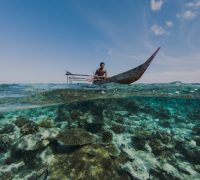Local Papuan fisherman Half Island Cenderawasih Bay West Papua Indonesia Using spear and outrigger canoe